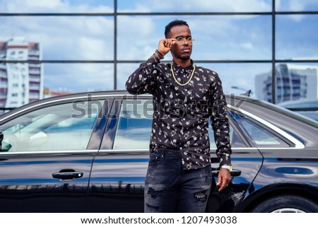 successful businessman handsome African American man in a stylish suit in brown jacket and glasses standing in front of a cool new black car on the street #1207493038