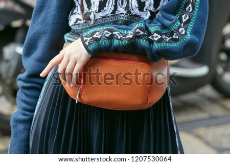 MILAN, ITALY - SEPTEMBER 21, 2018: Woman with orange leather Sportmax pouch and blue wool sweater before Marco de Vincenzo fashion show, Milan Fashion Week street style #1207530064