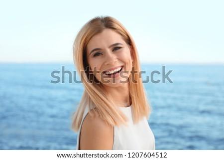 Portrait of beautiful blonde woman near sea #1207604512