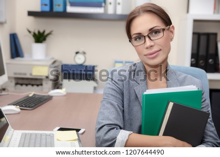Portrait of a nice office worker, pretty female with folders in hands at work place, successful business people life, female entrepreneur