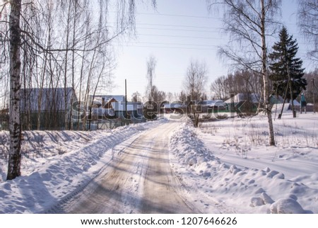 Snowy winter road in countryside leading to the houses #1207646626
