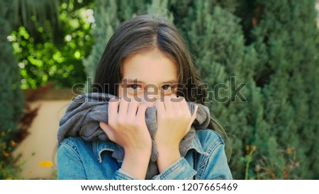 Portrait of beautiful young girl walking outdoors in autumn. She poses for the camera #1207665469