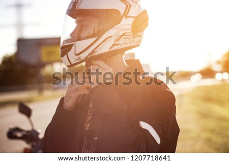 A handsome biker fastens his helmet. Putting on the helmet. Safety first. Close view on motorbiker's hands while he puts on his helmet. #1207718641
