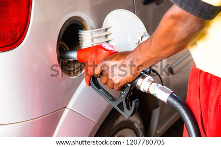 Hand of worker man refuelling a car at the petrol station. Concept photo for use of fossil fuels (gasoline, diesel) in combustion engines, air pollution and environment and occupational health. #1207780705