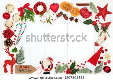 Christmas background border composition with traditional symbols of bauble tree decorations, candy canes, mince pies, fruit, spices, winter flora, ribbon and gift tag on rustic white wood. Top view. #1207802662