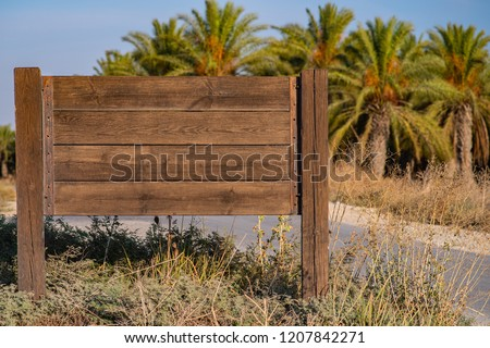 blank wooden road sign on palm plantation background. free space for text.