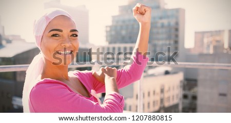 Strong woman wearing mantra scarf in the city with breast cancer awareness #1207880815