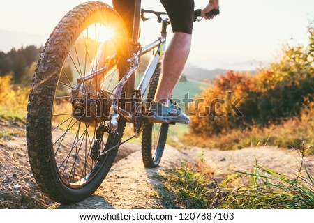 Mountain biker ride down from hill. Close up wheel image. Active and sport leisure concept #1207887103