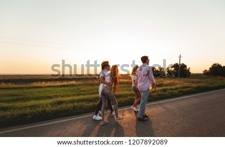 Company of happy young stylish guys walk along the road. on a sunny day #1207892089