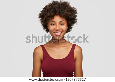 Headshot of successful smiling dark skinned sportswoman, knows how succeed, has toothy smile, dressed in casual vest, expresses good emotions, isolated over white background, feels carefree. #1207973527