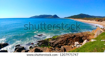 Caldeirao and Armacao beaches in Florianopolis, Brazil, during a sunny morning. Rocks can be seen close to the photographer, and mountains can be seen far away. #1207975747