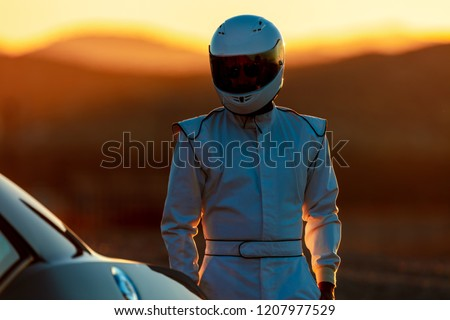 A Helmet Wearing Race Car Driver In The Early Morning Sun Looking At His Car Before Starting Royalty-Free Stock Photo #1207977529