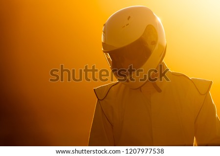 A Helmet Wearing Race Car Driver In The Early Morning Sun Looking At His Car Before Starting #1207977538
