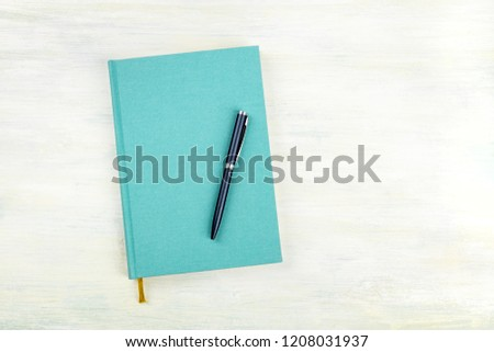 An overhead photo of a teal blue journal with a pen, an elegant notebook or planner with a place for text #1208031937