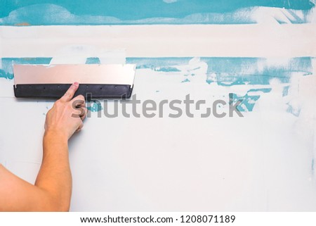 Hand with putty knife repair wall, Hand with a spatula, spatula with spackle paste structure, process of applying layer of putty trowel, working with spackling paste #1208071189