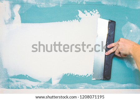 Hand with putty knife repair wall, Hand with a spatula, spatula with spackle paste structure, process of applying layer of putty trowel, working with spackling paste #1208071195