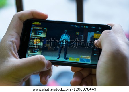 KUALA LUMPUR, MALAYSIA, OCTOBER 20 2018 : Selective focus hand holding a smartphone with Player's Unknown Battleground also known as PUBG online shooting gaming #1208078443
