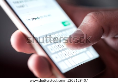 Man sending text message and sms with smartphone. Guy texting and using mobile phone late at night in dark. Communication or sexting concept. Finger typing with cellphone keyboard. Light from screen. #1208129407
