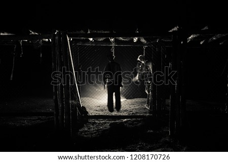 Horror view silhouette of hanged man on scaffold at night with fog and toned light on background. Execution (or suicide) decoration. Horror Halloween concept. #1208170726