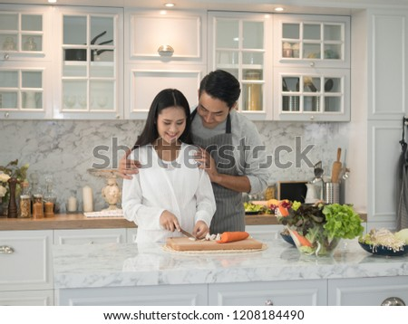 Young asian expecting pregnant couple cooking together in the kitchen at home. Pregnant woman preparing food with her husband.  #1208184490