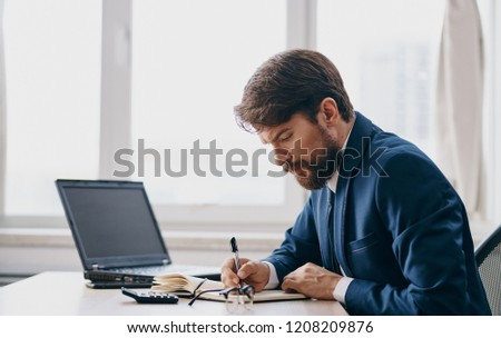 business man in a suit writes important information in a document                     #1208209876
