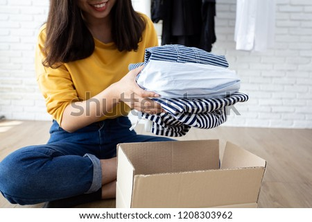 Woman holding Clothes with Donate Box In her room, Donation Concept. Royalty-Free Stock Photo #1208303962