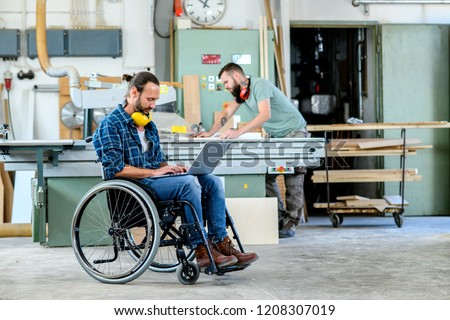 disabled worker in wheelchair in a carpenter's workshop with his colleague #1208307019