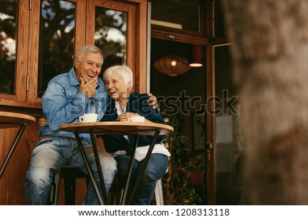 Senior couple in love sitting in cafe talking and having fun. Happy retirement couple relaxing at coffee shop. #1208313118