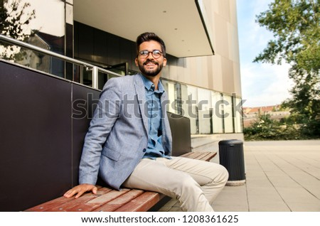 Handsome, elegant bearded man in suit, sitting on bench in front of modern office building and smiling  #1208361625