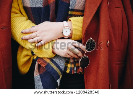 street style fashion details. close up, young fashion blogger wearing a sweater and a analog wrist watch. stylish woman checking the time on her watch. autumn/fall season.  #1208428540