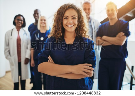 Young female doctor smiling while standing in a hospital corridor with a diverse group of staff in the background #1208448832