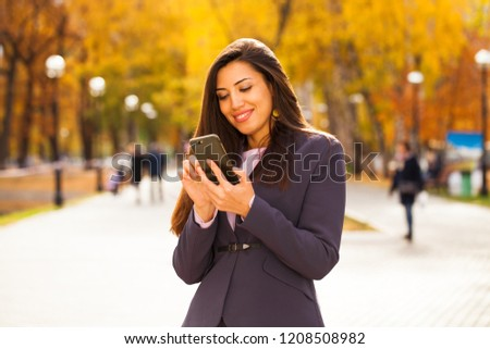 Woman calling by phone. Happy successful arab businesswoman in blue suit walking in autumn park #1208508982