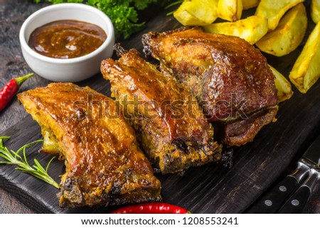 Barbecued pork ribs seasoned with a spicy bbq sauce served with fries on an old rustic wooden chopping board in a country kitchen #1208553241