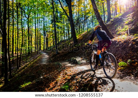 Cycling woman riding on bike in summer mountains forest landscape. Woman cycling MTB flow trail track. Outdoor sport activity. #1208555137