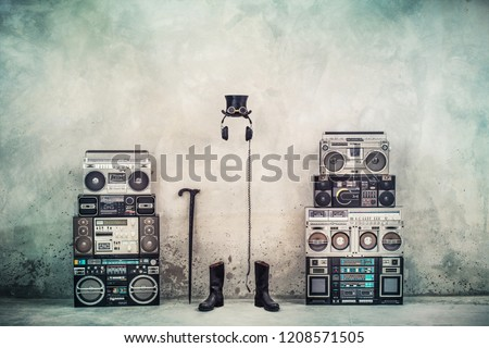 Retro old design ghetto blaster boombox radio cassette tape recorders, headphones, cylinder hat, leather boots, walking stick cane front concrete street wall. Vintage style filtered conceptual photo #1208571505