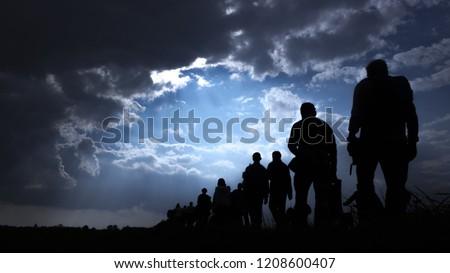 Sun rays illuminate people. Immigration of people. #1208600407