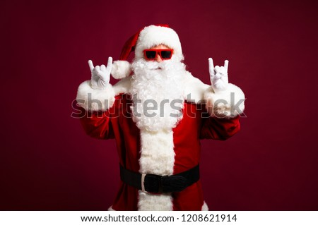 Excited grandfather Santa Claus is dancing and have a fun in sunglasses. Happy New Year, Merry Christmas, Celebration concept, travel, trips, party time, isolated on red background #1208621914