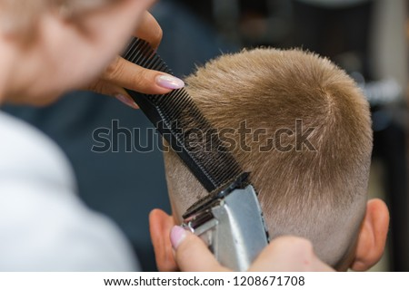 Make a fashionable haircut for children in the barbershop. Cut the hair with a typewriter. Hair Cutting Tool #1208671708