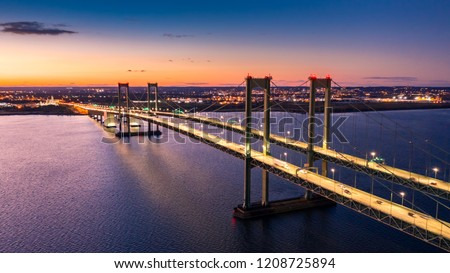 Aerial view of Delaware Memorial Bridge at dusk. The Delaware Memorial Bridge is a set of twin suspension bridges crossing the Delaware River between the states of Delaware and New Jersey #1208725894