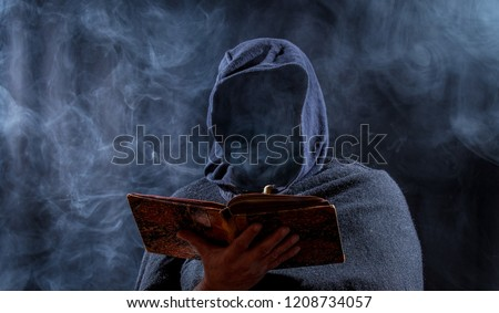 a man hides his face and reads in a book #1208734057