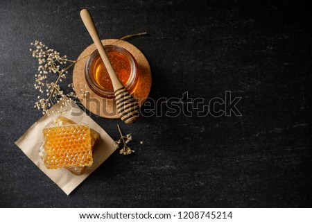 Honey bee and Honeycomb with honey dipper and dry flower on black background, bee products by organic natural ingredients concept #1208745214
