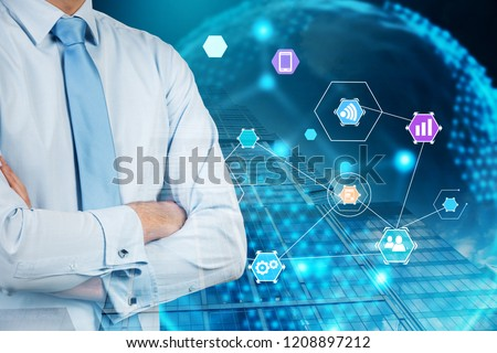Unrecognizable businessman in white shirt and blue tie standing with crossed arms near earth hologram with internet of things icons. Toned image double exposure #1208897212