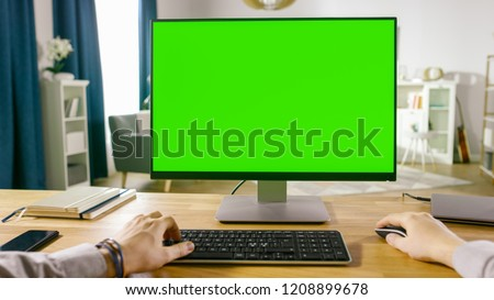 First Person View of Professional Freelancer Working on Green Mockup Screen Personal Computer From Home. Close-up POV Shot. In the Background Cozy Living Room.