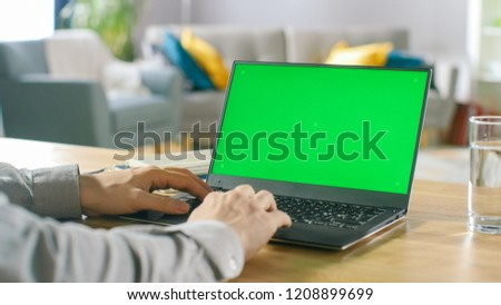 Close-up of a Man Uses Laptop with Green Mock-up Screen While Sitting at the Desk in His Cozy Living Room.