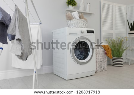 Laundry room interior with washing machine near wall #1208917918