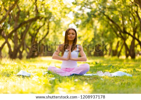 Woman resting in the park lying on the grass with a laptop and listening to music #1208937178