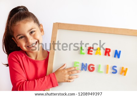 Language education concept. Learn English. Do you speak English. Cute little child girl with letters on the blackboard. English language school. English for children. Royalty-Free Stock Photo #1208949397