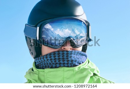 Close up of the ski goggles of a man with the reflection of snowed mountains.  A mountain range reflected in the ski mask.  Portrait of man at the ski resort on the background of mountains and sky #1208972164