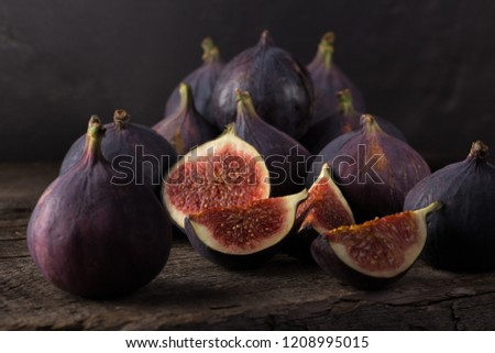 Fresh figs. A few figs on an old wooden background. Whole figs and one fig sliced. Autumn dish. Everyday autumn kitchen. Autumn harvest. Free space for text. #1208995015