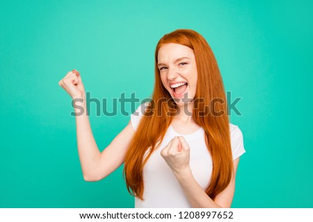 Portrait of nice positive glad cool cheerful attractive cute bright vivid shiny red straight-haired girl in casual white t-shirt, opened mouth, winning gesture, isolated on turquoise green background #1208997652
